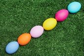 Line of painted eggs on green grass