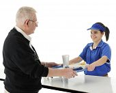 A happy teen worker happily serving a burger meal to a senior adult man.  On a white background.