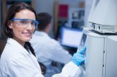 Smiling young chemist using the machine in the laboratory