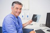 Portrait of a smiling dentist holding x-ray in dental clinic