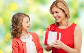 people, holidays, christmas and family concept - happy mother and daughter giving and receiving gift box over green lights background