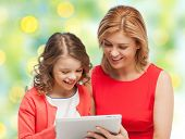 family, technology, people and christmas holidays concept - happy mother and daughter with tablet pc computer over green lights background