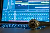 stock photo of workstation  - Microphone laying on laptop with digital audio workstation in background - JPG
