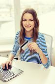 home, technology, banking, money and internet concept - smiling teenage girl with laptop computer and credit card at home