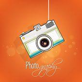 Creative photographic camera hanging on shiny orange background.