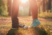foto of legs feet  - Young couple kissing in summer sun light - JPG