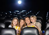 picture of watching movie  - Happy family of four having snacks while watching film in movie theater - JPG