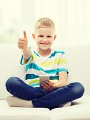 home, leisure, childhood, technology and internet concept - little boy with smartphone showing thumbs up at home