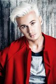 Close-up portrait of a beautiful young man with blond hair. Men's beauty, fashion.