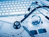 stock photo of stethoscope  - Stethoscope with financial statement on the desk - JPG