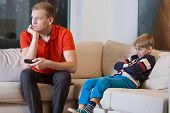 pic of boring  - Bored child and father is watching TV at home - JPG