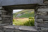 picture of derelict  - View of Welsh hillside with slate quarry through derelict window frame - JPG