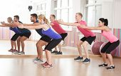 foto of squatting  - Fit people doing squats to strengthen legs - JPG