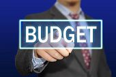 stock photo of budget  - Business concept image of a businessman clicking Budget button on virtual screen over blue background - JPG