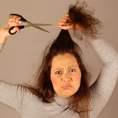 stock photo of scared  - The scared woman is cutting her hair - JPG