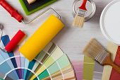 picture of interior decorator  - Painter and decorator work table with house project color swatches painting roller and paint brushes top view - JPG