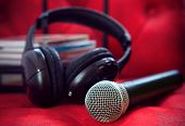 stock photo of karaoke  - microphone and head phone on red sofa leather use for entertainment and karaoke theme - JPG