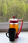 foto of kettles  - tea kettle and mug on home windowsill and view of spring green forest outdoors - JPG