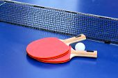 stock photo of ping pong  - Two table tennis or ping pong rackets and ball on blue table with net - JPG