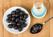 image of oil can  - Canned olives with pit in glass saucer spoon and bottle oil on wooden board - JPG