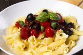 image of olive shaped  - a close up image of cooked Italian pasta with tomato and olives - JPG