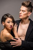 stock photo of tuxedo  - Young fashionable couple in tuxedos posing in the studio on dark background - JPG