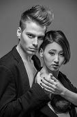 stock photo of tuxedo  - Young fashionable couple in tuxedos posing in the studio - JPG