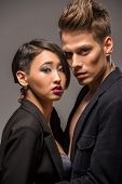 picture of tuxedo  - Young fashionable couple in tuxedos posing in the studio on dark background - JPG