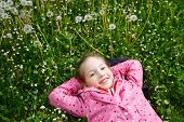 pic of dandelion seed  - Beautiful little girl lying in grass surrounded by dandelion seed heads enjoying nature and its serenity - JPG