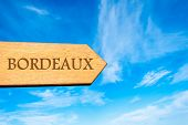 stock photo of bordeaux  - Wooden arrow sign pointing destination BORDEAUX FRANCE against clear blue sky with copy space available - JPG