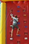picture of climbing wall  - boy climbing a wall to reach the top - JPG