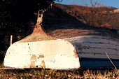 foto of old boat  - Old boat with cracked paint upturned on grass - JPG