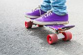 stock photo of snickers  - Feet of a riding skateboarder in a blue jeans and gumshoes selective focus with shallow DOF - JPG