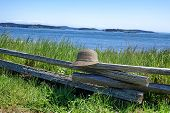 stock photo of split rail fence  - Image of a leisure hat resting on rustic wooden split rail fence with ocean and sky in background - JPG
