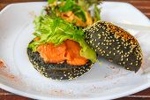 picture of charcoal  - Salmon and egg sandwich on a toasted charcoal bun with sesame seed in SIngapore on a plate decorated with paprika - JPG