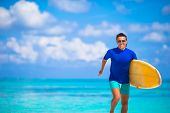 picture of rune  - Strong young surf man runing at the beach with a surfboard - JPG