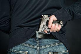 stock photo of handgun  - A person is hiding a handgun under the denim belt - JPG