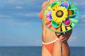 Closeup Of Woman In Orange Bikini Standing On Beach And Holding Pinwheel Toy, Sea And Sky