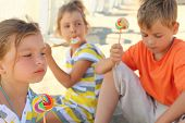 Serious Children Sitting On Beach And Eating Lollipops, Focus On Girl In Front