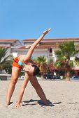 Young Beauty Woman Making Gym Exercises On Beach, House And Palms