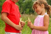Little Brother And Sister Play With Wooden Little Manikins In Nature. Focus On Manikins