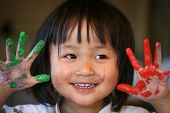 image of child development  - close up of chinese child face playing with playing with painting  - JPG