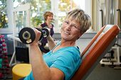 Happy Senior Female With Dumbbells