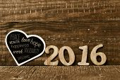 wooden numbers forming the number 2016 and a heart-shaped chalkboard with some wishes for the new ye poster