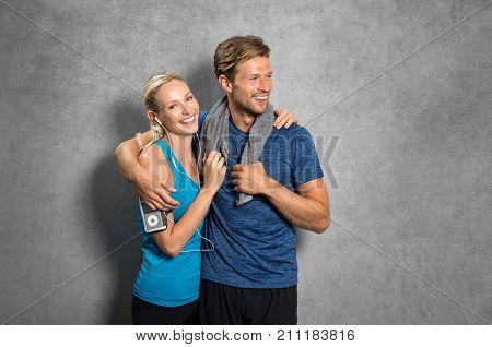 poster of Sports couple embracing over grey background. Happy young man and woman in sportswear leaning on wal