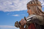 picture of armor suit  - Blonde girl in the Scandinavian suit on a blue sky background - JPG