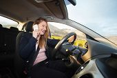 Young woman driving a car and talking on cellphone poster