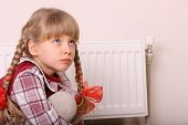 Sad girl sitting near heater. Children depression.