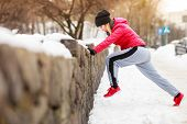 Woman Wearing Sportswear Exercising Outside During Winter poster
