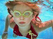 Child girl swim underwater in pool. Sport lesson.